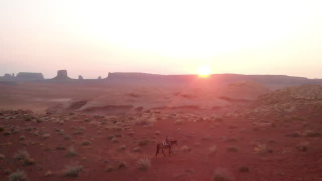 twelve year old native american navajo girl riding her horse bareback in the navajo indian reservation at monument valley tribal park at dusk in the summer with her dog following - wild west stock videos & royalty-free footage
