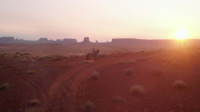 twelve year old native american navajo girl riding her horse bareback in the navajo indian reservation at monument valley tribal park at dusk in the summer with her dog following - utah stock videos & royalty-free footage