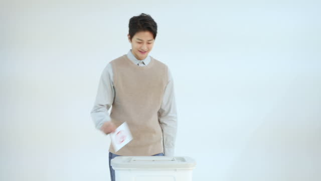 twenty year old young man walking to the ballot box and smiling brightly after voting - general election stock videos & royalty-free footage