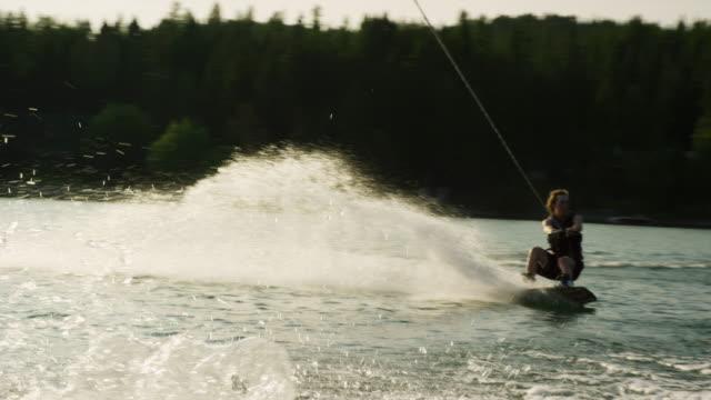 vídeos y material grabado en eventos de stock de un hombre caucásico veinteañera salta y realiza trucos en un wakeboard antes de caer en glen lake cerca de victor, montana en una tarde soleada - deporte acuático