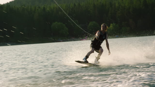 a twenty-something caucasian male jumps and performs tricks on a wakeboard on glen lake near victor, montana on a sunny afternoon - lake stock videos & royalty-free footage