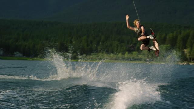 vídeos y material grabado en eventos de stock de un hombre caucásico veinteañón salta y realiza trucos en un wakeboard en glen lake cerca de victor, montana en una tarde soleada - deporte acuático