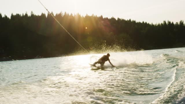 20代の白人男性がサニーアフタヌーンにモンタナ州ビクター近くのグレン湖のウェイクボードでジャンプしてトリックを実行します - ウェイクボーディング点の映像素材/bロール
