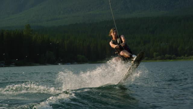 vídeos y material grabado en eventos de stock de un hombre caucásico veinteañera se levanta y salta y realiza trucos en un wakeboard en glen lake cerca de victor, montana en una tarde soleada - deporte acuático