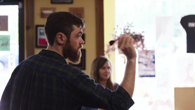 20-何か白人男のひげで目指すし、バーで若いブルネットの女性にダーツと笑顔がスローされます - ダーツバー点の映像素材/bロール