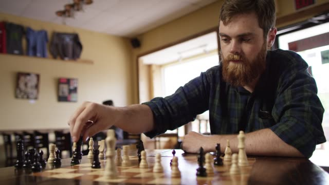 a twenty-something caucasian man with a beard moves his queen forward in a game of chess at a bar - chess stock videos & royalty-free footage