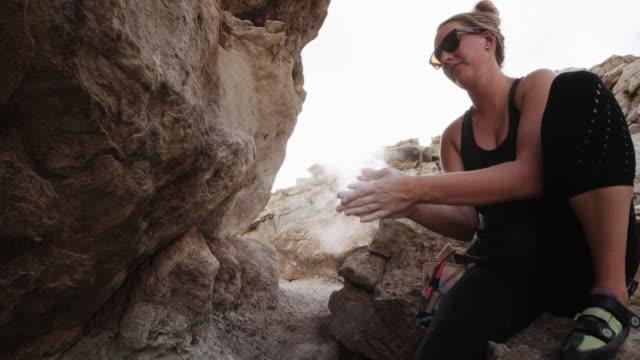 vídeos y material grabado en eventos de stock de a veinte-algo caucásica mujer se prepara para subir de la roca por marcar con tiza las manos - magnesio