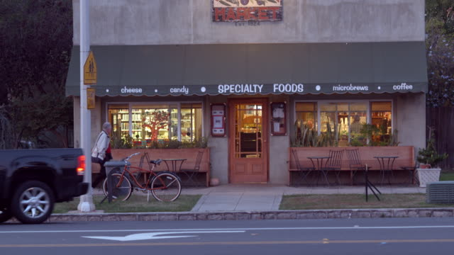 twilight exterior establishing shot of neighborhood coffee house and grocery store as pick up truck pulls away from curb / redlands, california, usa - facade stock videos & royalty-free footage