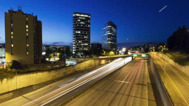 Twilight to night time lapse of a very broad section of freeway with free flowing traffic
