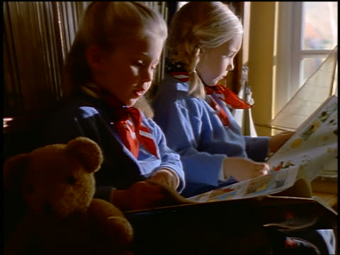 Twin blonde girls reading children's books by bookcase