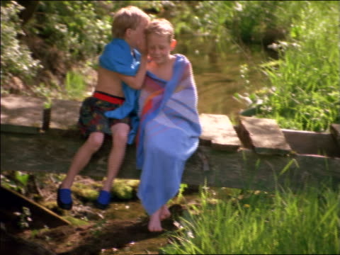 vidéos et rushes de 2 twin boys in swimsuits + towels sitting on footbridge over stream whispering - confidence