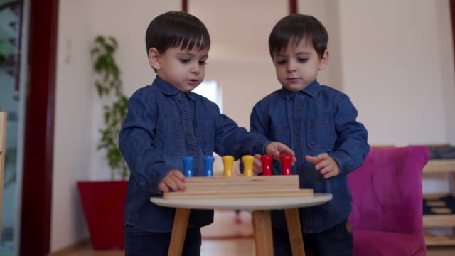 twin boys with matching outfits playing in daycare classroom - matching outfits stock videos & royalty-free footage