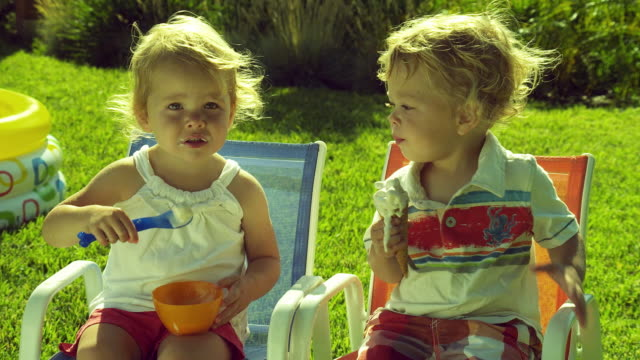 MS Twin children (2-3) sitting on chairs in backyard eating Ice Cream / Burbank, California, USA