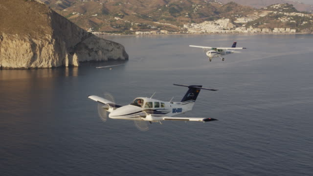 MS twin engine business aircraft and single engine training aircraft in flight along coastline, air-to-air view, RED R3D 4K