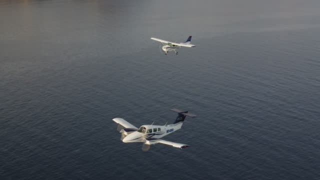 ms ha twin engine business aircraft and single engine training aircraft in formation flight over ocean, air-to-air view, red r3d 4k - air to air shot stock videos and b-roll footage