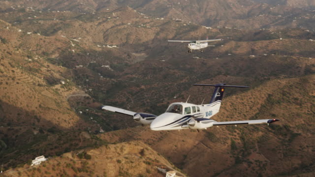 MS HA   twin engine business aircraft and single engine training aircraft  in formation flight over arid hilly landscape, air-to-air view, RED R3D 4K