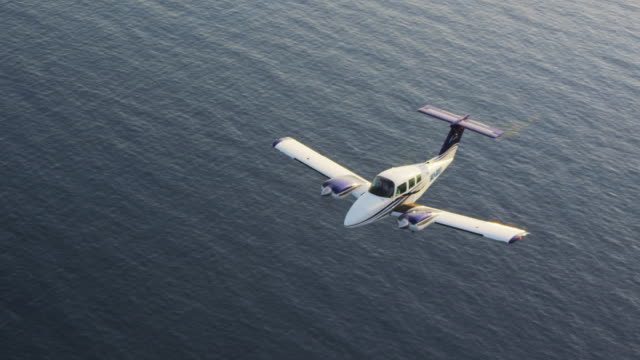 MS HA twin engine business aircraft in flight over ocean; airplane banks and exits frame right, air-to-air view, RED R3D 4K