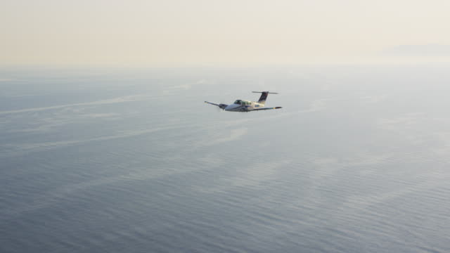 WS twin engine business aircraft in flight over ocean; air-to-air view, RED R3D 4K