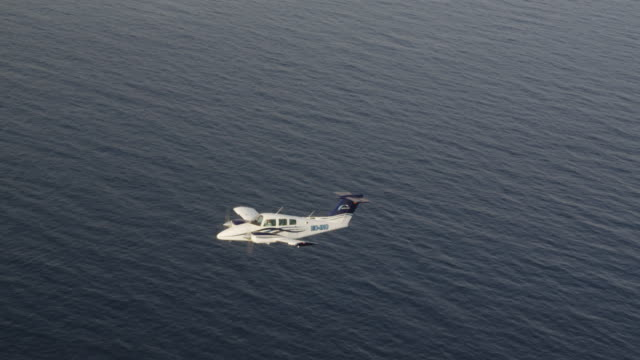 MS twin engine business aircraft in flight over ocean; air-to-air view, RED R3D 4K
