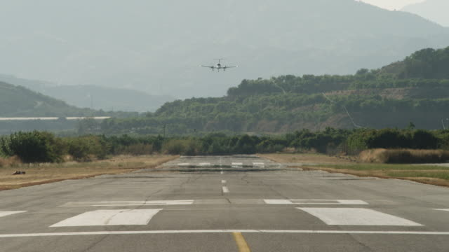 LS twin engine business aircraft performing touch and go landing , RED R3D 4K