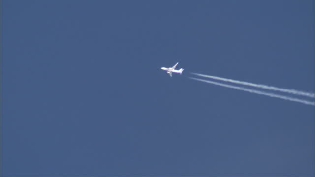 a twin engine jet leaves a double vapor trail as it streaks across a blue sky. available in hd. - track imprint stock videos and b-roll footage