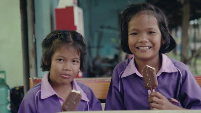Deux filles sont manger des glaces au parc