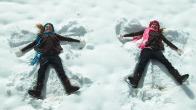 WS HA Twin girls (8-9) making snow angels / Cedar Hills, Utah, USA