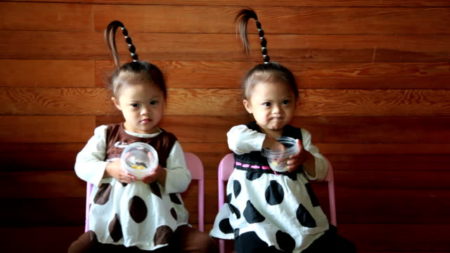 Twin girls with tall ponytails sit on folding chairs while eating snacks.