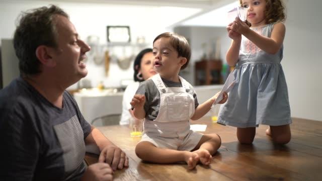 vídeos de stock, filmes e b-roll de irmão gêmeo (menino e menina da síndrome para baixo) que tem o divertimento com plano de papel - gaivota