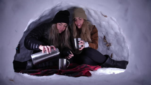 twin sister sitting in igloo as they pour hot chocolate into mugs - igloo stock videos & royalty-free footage