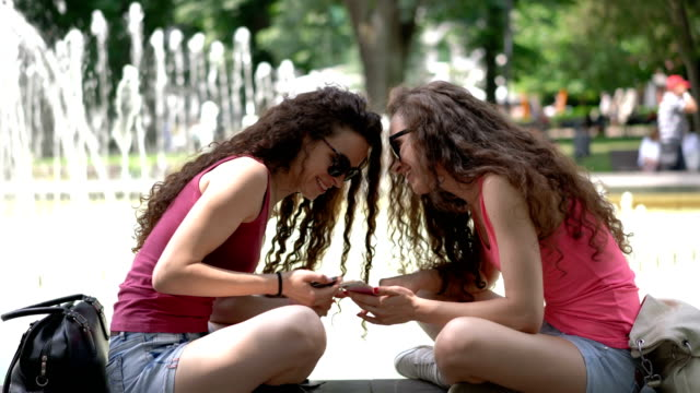 Deux soeurs jumelles de navigation sur leurs téléphones