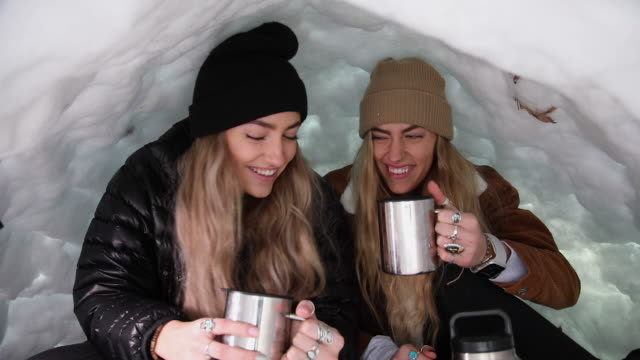 twin sisters cheering with mugs while in igloo - igloo stock videos & royalty-free footage