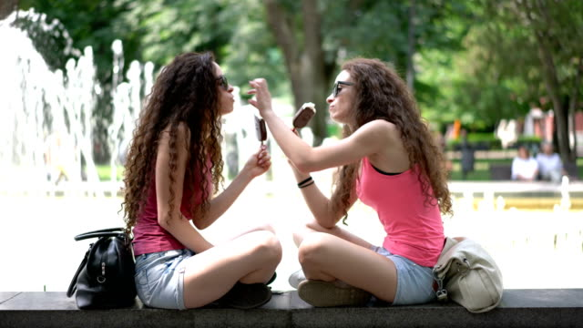 twin sisters eating ice-creams and making selfies with the phone - identical twin stock videos & royalty-free footage