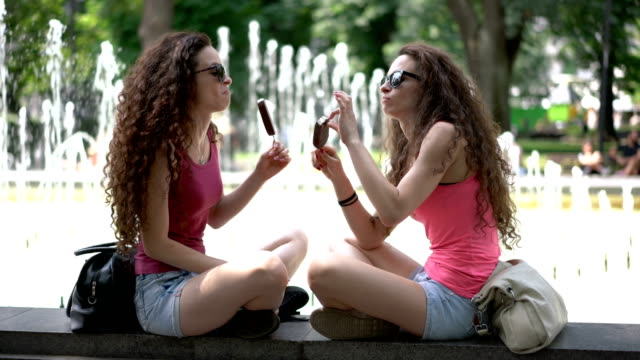 twin sisters eating ice-creams while sitting at the park fountains - twin stock videos & royalty-free footage