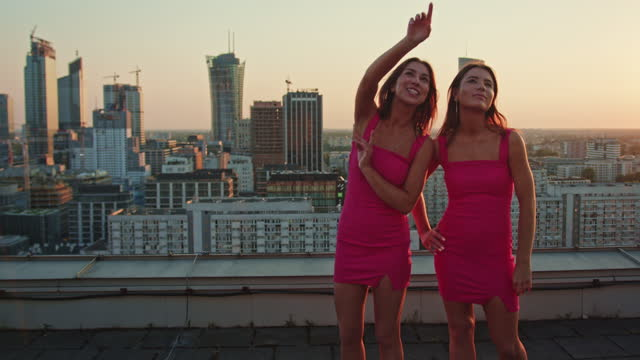vídeos de stock e filmes b-roll de twin sisters in pink enjoying rooftop view. city sunset - apontar sinal manual