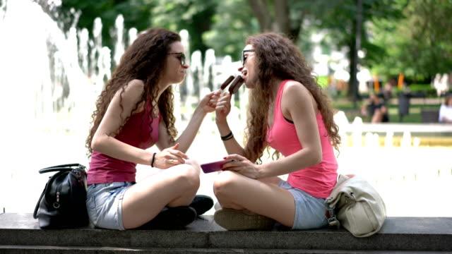 Zwillingsschwestern im Park essen Eis und Scherzen