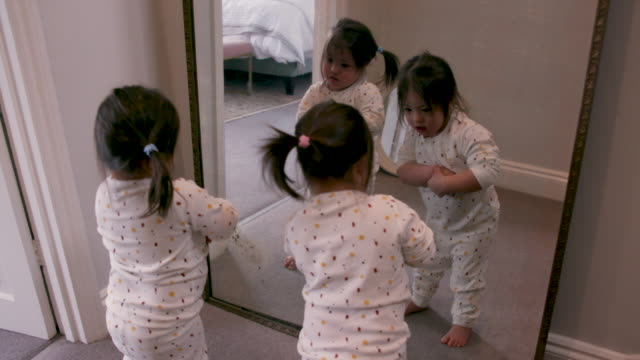 twin sisters looking at themselves in a mirror together at home - mirror stock videos & royalty-free footage