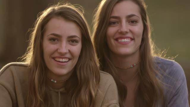 Twin teenage girls looking at camera and smiling