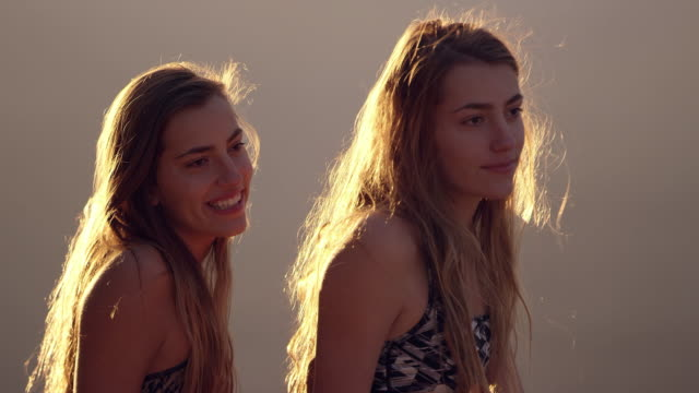 Twin teenage girls side by side looking into the distance
