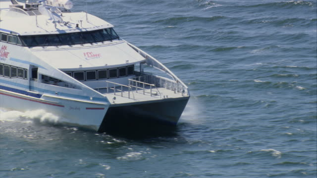 AERIAL Twin-hulled catamaran ferry crossing Nantucket Harbor, bow wave and wake streaming behind / Nantucket, Massachusetts, United States
