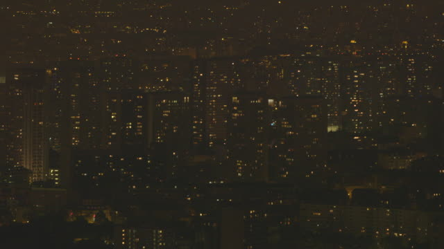twinkling lights blink on and off in an elevated wide shot of high-rise buildings in paris, france. - beliebiger ort stock-videos und b-roll-filmmaterial