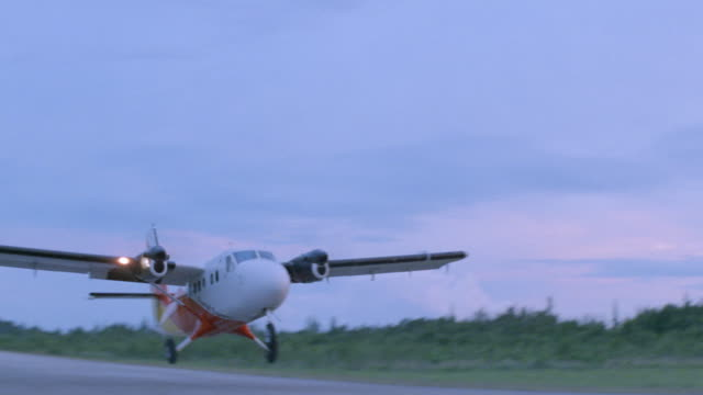 a twin-propeller airplane takes off from an airport runway. - propeller bildbanksvideor och videomaterial från bakom kulisserna