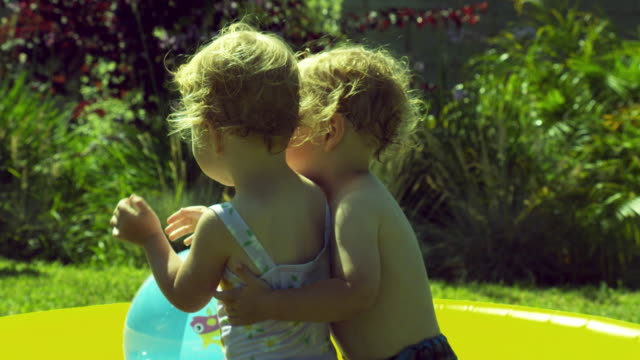 MS ZI Twins kids (2-3) playing in front of wading pool, boy gives girl hug and kiss / Burbank, California, USA