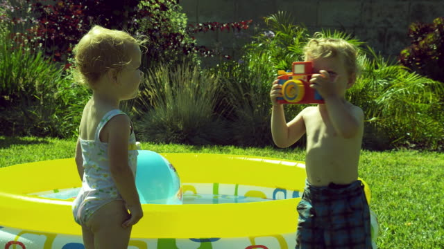 vidéos et rushes de ms twins kids (2-3) playing in front of wading pool, boy takes picture of girl with toy camera / burbank, california, usa - pataugeoire