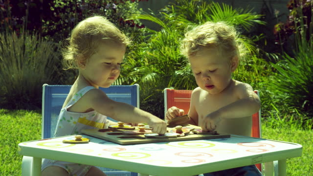 ms twins kids (2-3) sitting at table in backyard playing with puzzle / burbank, california, usa  - sibling stock videos & royalty-free footage
