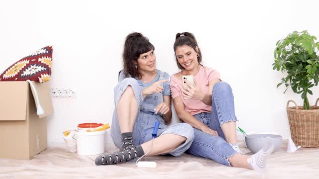 vídeos de stock, filmes e b-roll de gêmeos tirando uma selfie enquanto fazem uma pausa no trabalho doméstico em sua nova casa - duas pessoas