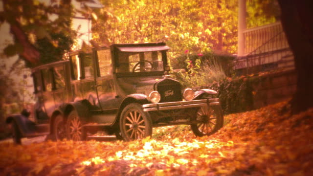 reenactment orange pan two 1920s cars (model t?) in front of house surrounded by fallen leaves in autumn - ford motor company stock videos and b-roll footage