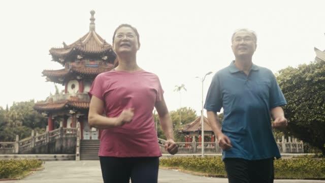 公園を歩く2人の現役アジアの高齢者パワーウォーキング - パワーウォーキング点の映像素材/bロール