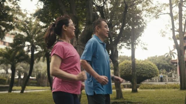 公園を歩く2人の現役アジアの高齢者パワーウォーキング(スローモーション) - パワーウォーキング点の映像素材/bロール