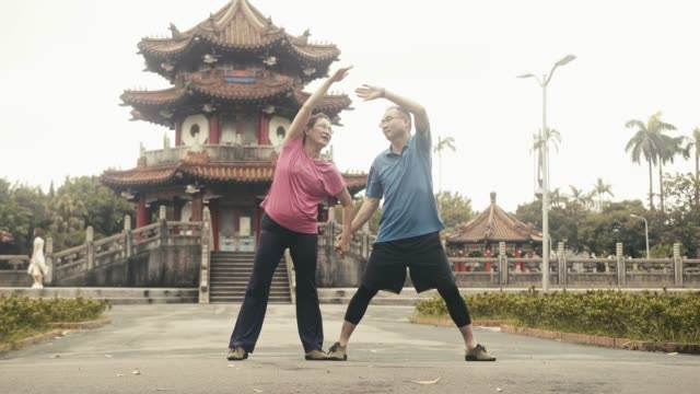 two active asian seniors stretching in local city park - pampering self stock videos and b-roll footage
